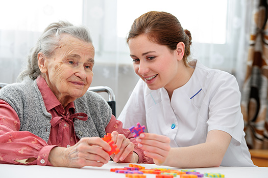 Senior-Woman-with-Dementia-Engaged-in-a-Puzzle-with-Caregiver