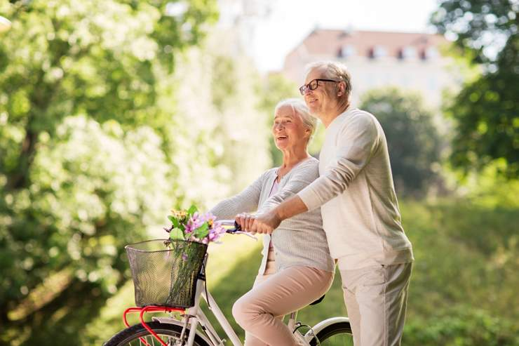 happy-senior-couple-with-bicycle-at-summer-park-PVKXH78